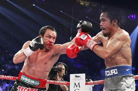 Juan Manuel Marquez (L) of Mexico punches at Manny Pacquiao of the Philippines during their welterweight fight at the MGM Grand Garden Arena in Las Vegas, Nevada December 8, 2012. REUTERS/Steve Marcus