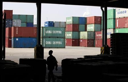 A worker walks in a shipping container area at the Port of Shanghai November 13, 2012. REUTER/Aly Song