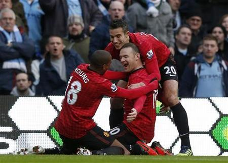 Manchester United's Wayne Rooney (C) celebrates his first goal against Manchester City with Robin Van Persie (R) and Ashley Young during their English Premier League soccer match at The Etihad Stadium in Manchester, northern England December 9, 2012. REUTERS/Eddie Keogh