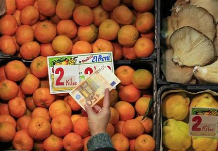 A man holds a 50 euro note at a grocery in the Pino Montano market of the Andalusian capital of Seville November 28, 2012. REUTERS/Marcelo del Pozo
