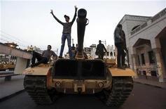"""Противники египетского президента Мохамеда Мурси стоят на танке возле президентского дворца в Каире 8 декабря 2012 года. Оппозиционная коалиция в воскресенье отвергла предложенный президентом Египта исламистом Мохамедом Мурси план, назвав намеченный на эту неделю конституционный референдум риском погрузить страну в """"насильственнную конфронтацию"""". REUTERS/Amr Abdallah Dalsh"""
