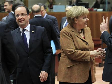 France's President Francois Hollande (L) walks past Germany's Chancellor Angela Merkel during a summit of European Union leaders discussing the European Union's long-term budget in Brussels November 22, 2012. REUTERS/Yves Herman