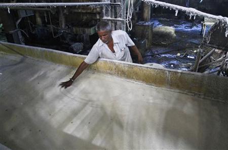 A worker spreads sugar inside a sugar factory at Sanyan village in Gujarat April 23, 2012. REUTERS/Amit Dave/Files
