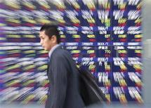Мужчина проходит мимо табло с котировками у биржи в Токио 18 ноября 2010 года. Азиатские фондовые рынки кроме Южной Кореи выросли в понедельник благодаря макроэкономическим показателям Китая. REUTERS/Kim Kyung-Hoon