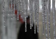 Мужчина идет по улице на фоне свисающих сосулек в Москве 22 февраля 2012 года. Рабочая неделя в Москве будет морозной, ожидают синоптики. REUTERS/Sergei Karpukhin