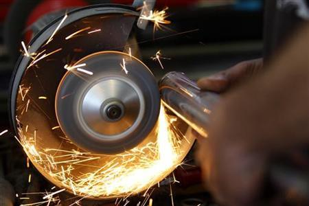 A worker cuts iron in his repair shop in Rome April 18, 2012. REUTERS/ Max Rossi