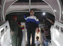El presidente venezolano, Hugo Chávez, llegó a Cuba para someterse a su cuarta cirugía por el cáncer que padece desde 2011 y prometió volver pronto, tras haber admitido que su enfermedad podría adelantar el fin de su era de 14 años al frente del país petrolero. En la imagen, Hugo Chávez se despide antes de partir a Cuba en Caracas, el 10 de diciembre de 2012. REUTERS/Miraflores Palace/Handout