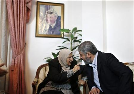 Hamas chief Khaled Meshaal speaks with Kadejah, the sister of late Palestinian leader Yasser Arafat (pictured on the wall), in Gaza City December 9, 2012. REUTERS/Mohammed Salem