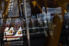 A pesar de seguir frontalmente enfrentados con la dirección de Iberia por sus planes de reestructuración, los sindicatos de la aerolínea desconvocaron el lunes las jornadas de huelga convocadas para el tradicionalmente ocupado mes de diciembre. En la imagen, aviones de Iberia y un pasajero reflejado en una cristalera en Barajas, el 29 de noviembre de 2012. REUTERS/Susana Vera