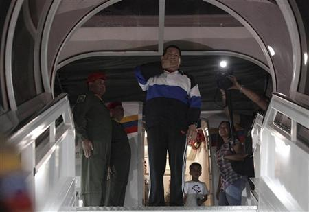Venezuelan President Hugo Chavez blows a kiss from the door of the airplane before departing to Cuba at Simon Bolivar airport in Caracas December 10, 2012. REUTERS/Miraflores Palace/Handout