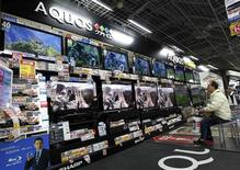 A man watches Sharp's television sets at an electronic shop in Tokyo in this March 19, 2012 file photo. REUTERS/Kim Kyung-Hoon/Files