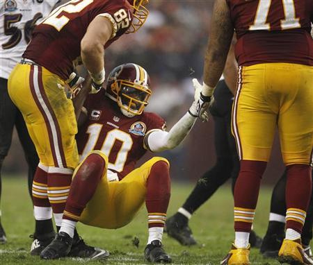 Washington Redskins quarterback Robert Griffin III (C) is helped up by teammates after being tackled by the Baltimore Ravens defense in the second half of their NFL football game in Landover, Maryland December 9, 2012. REUTERS/Gary Cameron