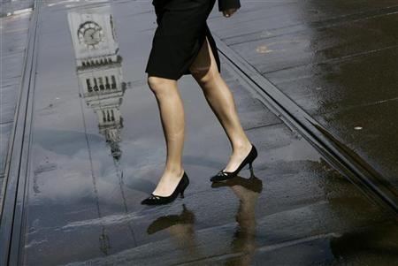 A woman is reflected in a rain puddle along with the Ferry Building following a steady rain in San Francisco, California March 2, 2009. REUTERS/Robert Galbraith