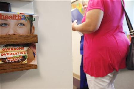 Carolyn Dawson, bariatric surgery patient walks by a copy of ''health2you'' magazine with a cover story on how to overcome overeating at the Rose Medical Center in Denver for her pre-op appointment five days before her procedure August 25, 2010. REUTERS/Rick Wilking/Files