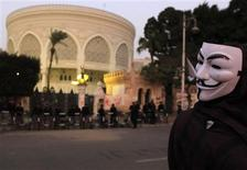 An Anti-Mursi protester, wearing a Guy Fawkes mask, stands in front of the presidential palace in Cairo December 10, 2012. Egypt's Islamist President Mohamed Mursi has given the army temporary power to arrest civilians during a constitutional referendum he is determined to push through despite the risk of bloodshed between his supporters and opponents accusing him of a power grab. REUTERS/Mohamed Abd El Ghany