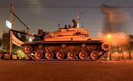 A man walks past an army tank from the republican guard in front of the presidential palace in Cairo December 10, 2012. REUTERS/Mohamed Abd El Ghany (EGYPT - Tags: POLITICS CIVIL UNREST MILITARY)