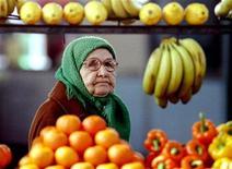 Пожилая женщина смотрит на прилавок с овощами и фруктами на московском рынке 11 мая 1994 года. Пик роста потребительских цен в России пройден, полагает Центробанк. REUTERS/Viktor Korotayev
