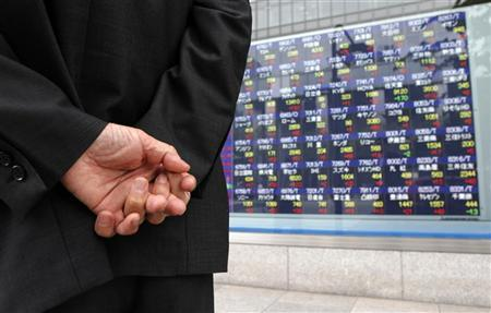 A man looks at a stock index board outside a brokerage in Tokyo June 6, 2012. REUTERS/Kim Kyung-Hoon/Files
