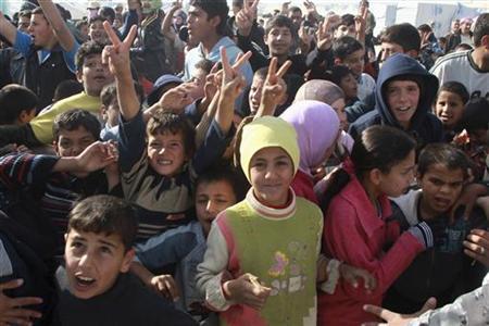 Syrian refugees react as United Nations (U.N.) Secretary-General Ban Ki-moon arrives to visit a U.N.-run school in Al Zaatri refugee camp, in the Jordanian city of Mafraq, near the border with Syria December 7, 2012. REUTERS/Muhammad Hamed