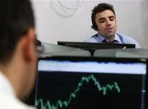 En un clima de relativa estabilidad financiera, el Tesoro Público español dijo el martes que colocó más del objetivo máximo establecido de 3.500 millones de euros en letras a largo plazo con una reducción de su coste financiero. En la imagen, varios operadores durante la subasta de bonos en Madrid el 5 de diciembre de 2012. REUTERS/Andrea Comas