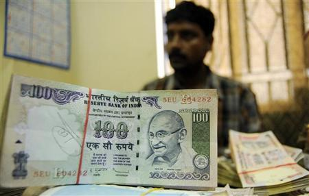An employee arranges Indian currency notes at a cash counter inside a bank in Agartala, Tripura, June 3, 2010. REUTERS/Jayanta Dey/Files