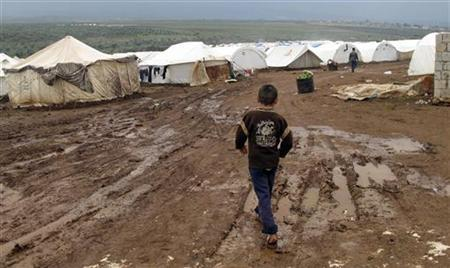 A Syrian refugee boy walks through mud at a refugee camp in Atimeh, on the Syrian-Turkish border of the Idlib Governorate December 10, 2012. Picture taken December 10, 2012. REUTERS/Abdalghne Karoof (SYRIA - Tags: CONFLICT SOCIETY)