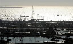 Вид на нефтегазовые промыслы в Каспийском море в районе Баку 12 октября 2004 года. BP устранила возникшие в ноябре технические проблемы на одной из пяти скважин на крупнейшем в Азербайджане месторождении газа, каспийском Шах-Дениз, и во вторник восстановила добычу со всех скважин. REUTERS/Grigory Dukor