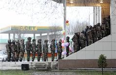 Казахские пограничники выстроились в очередь на избирательный участок в селении Кордай 3 апреля 2011 года. Военный суд в Казахстане оставил за решеткой пожизненно 20-летнего пограничника, признав виновным в расстреле весной 14 сослуживцев и егеря на отдаленной заставе у границы с Китаем. REUTERS/Vladimir Pirogov