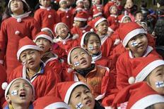 Los países asiáticos relativamente ricos, incluidos Corea del Sur y Singapur, así como Hong Kong, lideran un ránking internacional de rendimiento en los estudios, un resultado que los investigadores dijeron reflejaba un fuerte compromiso social con la educación primaria. En la imagen, varios estudiantse vestidos de Papa Noel en Nanjing (China) el 7 de diciembre de 2012. REUTERS/Sean Yong