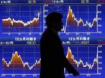 El Índice Nikkei cerró al máximo de casi ocho meses el miércoles por la influencia de los exportadores y las persistentes especulaciones de que un nuevo gobierno japonés presionaría al banco central para que adopte medidas de política monetaria de mayor alcance. En la imagen de archivo, un hombre pasa junto a un panel electónico con cotizaciones en Tokio, el 22 de noviembre de 2012. REUTERS/Kim Kyung-Hoon