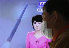 Житель Южной Кореи стоит около телевизора в Сеуле, передающего новость о том, что КНДР запустила ракету, 12 декабря 2012 года. Северная Корея провела в среду успешный пуск ракеты, укрепив авторитет своего недавно взявшего бразды правления лидера Ким Чен Ына и подтвердив исходящую от государства-изгоя угрозу его противникам. REUTERS/Lee Jae-Won