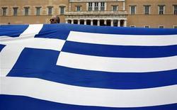 """Участник акции протеста держит в руках флаг Греции в Афинах 10 февраля 2012 года. Обратный выкуп греческих облигаций всего лишь незначительно не достиг запланированных целей, но оставил финансовую """"дыру"""" в размере 450 миллионов евро в плане сокращения задолженности страны. REUTERS/Yiorgos Karahalis"""