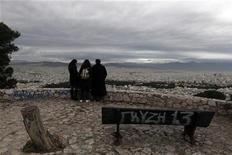 Женщины смотрят на Афины с горы Ликавит 11 декабря 2012 года. Греция получила предложения на сумму 31,9 миллиарда евро в рамках обратного выкупа облигаций и одобрит все заявки, если международные кредиторы увеличат финансирование этой схемы на 1,29 миллиарда евро. REUTERS/John Kolesidis