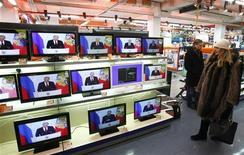 Люди смотрят выступление президента России Владимира Путина в магазине в Москве 12 декабря 2012 года. Президент Владимир Путин выступил с первым после возвращения в Кремль посланием парламенту. Речь президента длилась 80 минут, большую её часть он посвятил идеологии и демографии. REUTERS/Mikhail Voskresenskiy