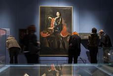 People stand in front of a portrait of Peter the Great at the Russians and Germans exhibition at the New Museum in Berlin, December 2, 2012. REUTERS/Thomas Peter