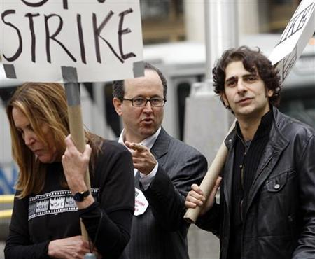 Jonathan Tasini (C), president emeritus of the National Writers Union, speaks with actor and writer Michael Imperioli (R), known for his work on the television program 'The Sopranos,' as they walk the picket lines for the striking Writers Guild of America, in New York, November 13, 2007. REUTERS/Chip East/Files