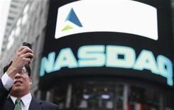 Мужчина делает фотографию около биржи Nasdaq в Нью-Йорке, 23 июля 2012 года. Nasdaq OMX Group Inc купит отделения Thomson Reuters Corp по связям с общественностью и инвесторами за $390 миллионов, сообщил биржевой оператор, стремящийся диверсифицировать операции за счет деятельности, не зависящей от дилинга. REUTERS/Brendan McDermid