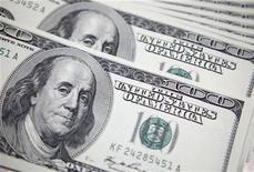 Долларовые купюры в банке в Сеуле 20 сентября 2011 года. Доллар снижается после объявления Федеральной резервной системы о новой программе приобретения облигаций, но иена близка к девятимесячному минимуму к доллару на фоне ожиданий смягчения политики центробанка Японии. REUTERS/Lee Jae-Won