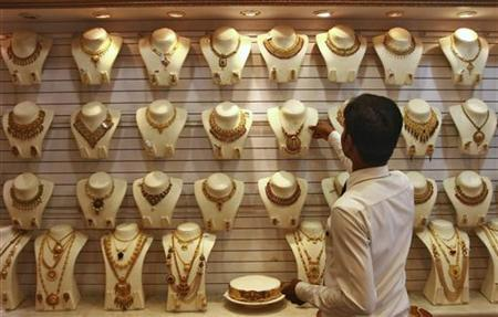 A salesman arranges a gold necklace inside a gold jewellery showroom in Kochi April 16, 2012. REUTERS/Sivaram V/Files