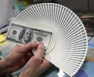 """Сотрудница обменного пункта держит веер из 100-долларовых курюр в Токио, 27 ноября 2009 года. Доллар растет в четверг, так как инвесторы переварили новости от Федеральной резервной системы и решили зафиксировать прибыль, ликвидируя """"короткие"""" долларовые позиции. REUTERS/Yuriko Nakao"""