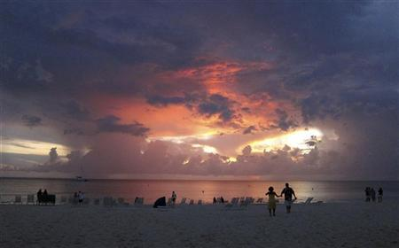 Tourists walk on Seven Mile Beach at sunset in George Town, Cayman Islands July 28, 2011. REUTERS/Gary Hershorn/Files