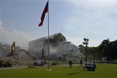 Haiti's national flag flies above the collapsed cupola of its condemned National Palace during demolition in Port-au-Prince September 12, 2012. REUTERS/Swoan Parker