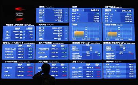 A visitor looks at a screen displayed market indices from around the world and foreign currency rates against the Japanese yen at the Tokyo Stock Exchange in Tokyo November 5, 2012. REUTERS/Issei Kato/Files