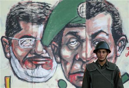 A soldier stands in front of a mural depicting Egypt's former President Hosni Mubarak (R), former Field Marshal Mohamed Hussein Tantawi (C) and Egypt's President Mohamed Mursi drawn on the wall of the presidential palace in Cairo December 12, 2012. Egypt's liberal and secular opposition said on Wednesday it would back a ''no'' vote in a referendum on a divisive new constitution promoted by Islamist President Mursi, calling off a boycott as long as safeguards are in place for a fair vote. REUTERS/Khaled Abdullah (EGYPT - Tags: POLITICS CIVIL UNREST MILITARY)