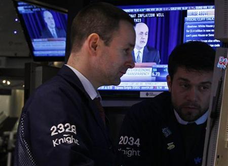 Traders work on the floor of the New York Stock Exchange while a screen shows U.S. Federal Reserve Chairman Ben Bernanke's news conference, December 12, 2012. Stocks ended little changed on Wednesday, giving up most of the day's gains after Bernanke reiterated that monetary policy won't be enough to offset damage from the ''fiscal cliff.'' REUTERS/Brendan McDermid (UNITED STATES - Tags: BUSINESS POLITICS)