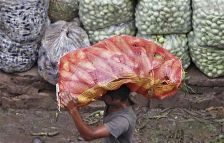 A man carries a sack filled with maize at a wholesale vegetable market in Ahmedabad August 14, 2012. REUTERS/Amit Dave/Files