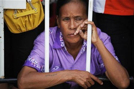A migrant worker sits behind a security fence as she waits with others for Myanmar's pro-democracy leader Aung San Suu Kyi to arrive at the Nationality Verification Centre for migrant workers from Myanmar in Samut Sakhon province May 31, 2012. REUTERS/Damir Sagolj/Files