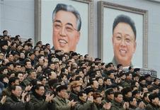 Norte-coreanos aplaudem diante de retratos do fundador do país, Kim Il-sung (E), e do líder Kim Jong-il, que faleceu, durante comício para comemorar lançamento de foguete.14/12/2012 REUTERS/Kyodo