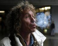 55-year-old homeless Honza B. smokes a used cigarette butt as he escorts his tour group in Prague October 26, 2012. Honza B. works for a student-run tour agency Pragulic as a tour guide that shows tourists the sides of Prague that sightseers would normally avoid. REUTERS/Petr Josek