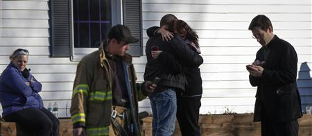 Family members embrace near Sandy Hook Elementary School, where a gunman opened fire on school children and staff in Newtown, Connecticut December 14, 2012. REUTERS-Adrees Latif